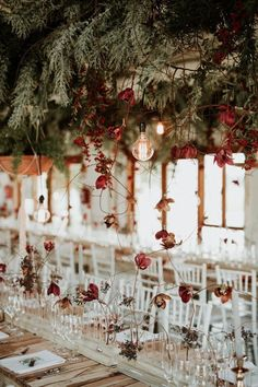 Stunningly beautiful wedding reception floral decor with a wild, red, and wintery hanging design | image by Dearheart Photography #weddingphotoinspiration #weddingphotoideas #centerpieces #reception #weddingreception #weddingreceptioninspo #receptioninspiration #receptiondecor #receptioninspo #finishingtouches #weddingdecor #tablescape #floraldesign