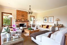 Sala de estar com lareira em casa de campo. Decoração prioriza revestimentos naturais e elementos artesanais para criar ambiente aconchegante. Almofadas de tricô realçam o decor. Projeto de design de interiores em Campos do Jordão.