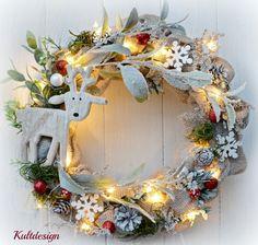 Vánoční věnec Zasněžený jelen s LED osvětlením Vánoční jutový věnec na dveře nebo do interiéru v klasickém stylu dekorovaný roztomilým dřevěným jelenem ( nebo sobem?) , umělými květinami se zasněženým efektem a ozdobnými komponenty. Věnec je opatřen LED světýlky na 3 AA baterie Použité barvy:  béžová , , zelená, bílá, čevená Rozměry: 38 cm...