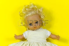 vintage doll dolly puppet old toy retro yellow background blue eyes blond hair infant infantile chil Stock Photo