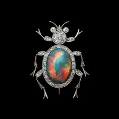 Black Opal Beetle Brooch by Chaumet. Platinum mille-grain brooch, diamonds outlining the oval black opal body, and set in the head, antennae, eyes and tapering legs.