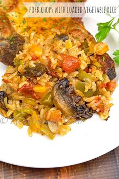 Delicately flavored pork chops bake right on top of this loaded vegetable rice medley. This rice is definitely the star of this show!