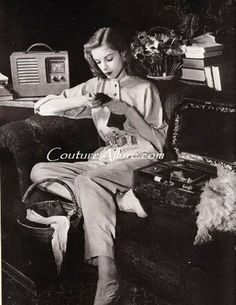 Bacall poses as a woman engaged in wartime evening activities: listening to the radio while darning socks. She wears lounging pajamas in grey wool/rayon by Claire McCardell.