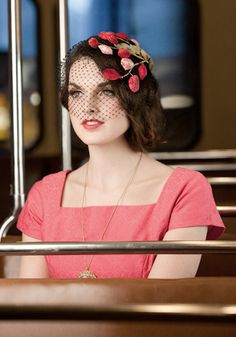"Vintage Postscript Fascinator. ""Veil my eyes, veil my tears - that's how much I am missing you."" This pretty black veiled fascinator features an ornate light pink, deep fuchsia, and warm olive green floral stem embellishment across the center front.  #modcloth"