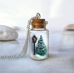 This snow globe bottle necklace features a scene from The Chronicles of Narnia - a street lamp in the middle of a snowy forest.