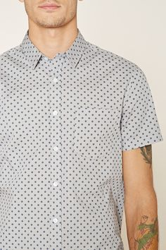 A fitted woven shirt with an allover ornate print, a basic collar, a buttoned front, a chest patch pocket, and short sleeves.