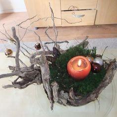 soort bloemstuk van takken uit het bos en sterretjesmos en een kaars erin en kerstballen en dennenappels