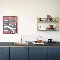 Over the counter is a framed vintage poster from the Centre Pompidou and on the counter is a large ceramic Midnight Blue Bowl from the Stilleben line of tableware and a Skagerak Edge Teapot on a Cassette Tray.