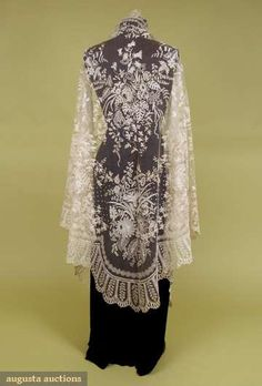 "BRUSSELS LACE APPLIQUE SHAWL, 1880-1900  Triangle of cream cotton net w/ hand done Brussels bobbin lace in floral patterns, 50"" x 106"" (many scattered tiny & small holes in net, few small brown stains) net fair, lace excellent."