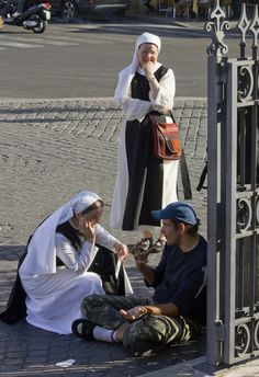Two religious sisters engaged in conversation with a beggar outside Santa Maria Maggiore.