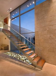 Open riser staircase having elegant narrow stringers with attached glass paneled railing.
