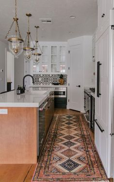 BECKI OWENS— Project Reveal: Spanish Modern Kitchen. Kitchen features black and white tuxedo cabinetry, Benjamin Moore Chantilly Lace, Benjamin Moore Onyx, bronze and brass mixed metals, vintage kilim runner, and patterned cement tile backsplash.