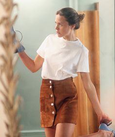 Suede mini, white tee end loose updo. Image via LA COOL & CHIC