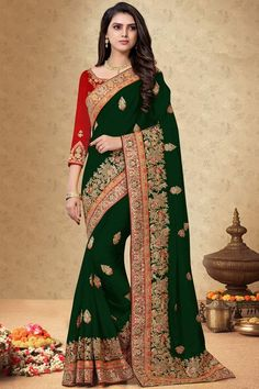 Dark Green silk saree with red silk blouse, embellished with dori work, resham work and sequins work. Saree with Round Neck, Quarter Sleeve. It comes with unstitch blouse, it can be stitched 32 to 58 sizes. # dark green #silk # wedding wear #saree #blouse #Andaazfashion #UK