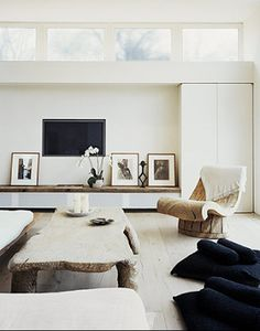 Who says a chair has to look like a chair --- I want to go sit in that one! In this sleek-looking living room, even the art is neatly propped again the fireplace surround. Love the windows on that wall!