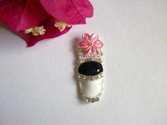 1x bijou d'ongle couverture complète métal argenté, fond noir et blanc avec strass brillants avec une fleur rose qui arrive au dessus de l'ongleSur ongles naturels (avec de la colle pour capsules)ou sur faux ongles en gel uvou résine acrylique