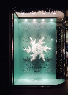 Embedded in - its corporate color- mint green patterns, the two eye-catching, slowly rotating snowflakes attract the passersby eyes not only to the precious perfumes, placed on little gondolas hanging on the flakes branches, but to the entrance of the christmassy decorated store.