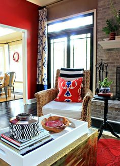 stenciled drop cloth curtains, fun red and blue pillows and black window trim.