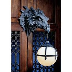 """Tales of mythical Marshgate Castle tell of dragon trophies lining its long, echoing chambers. Electrify your own castle walls with our intricately sculpted designer resin dragon that stands a full 15"""" from the wall and holds a hanging 6"""" dia. glass orb from its menacing mouth."""