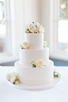 For a wedding cake that's all about modern elegance, choose a sleek all-white design, accented with real white flowers.