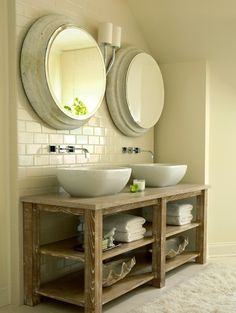 Stunning bathroom with salvaged wood double bathroom vanity, twin glossy white vessel sinks, polished nickel wall-mount faucets, gray washed round mirrors
