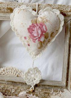 Závěsné srdíčko s růžičkami Závěsná dekorace je ušita z bavlněné látky sse vzorem růžiček. Obháčkování bavlněnou přízí, ze které je uháčkována i kytička. Zdobení dřevěný korálek. Průměr 11 cm
