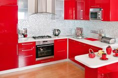 This kitchen is a little more on the modern side, and has a lot more color. The cabinets are a glossy fire-engine red, which contrasts beautifully with the pristine white countertops and gray glass tile backsplash. The high-end appliances are in stainless steel.