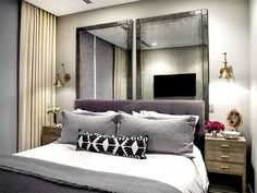 Glamorous and small bedroom with gray bedding, patterned pillows, and mirrors behind headboard