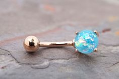 """Synthetic aqua blue opal belly button jewelry ring. The 8mm aqua opal is prong set and glows in the light with radiant iridescence. The opal belly ring is 14 gauge and 3/8"""" long (10mm), and is made of"""