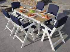 Nautical 7-Piece Dining Set. Features chairs that can fold flat for easy transportation and storage. Made from recycled plastic lumber. Available in 7 colors and a variety of cushion options.