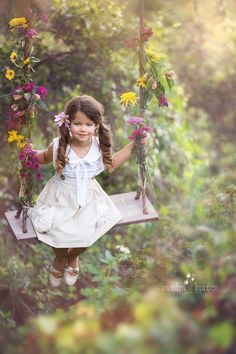 Sandra Bianco Photography specializes in photography of children. Pin comes from Sandra Bianco's own website. © Sandra Bianco Photography March in which a girl with long, brown pigtails is swinging on a swing decorated with flowers
