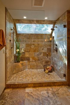This breathtaking shower achieves an effortlessly elegant look. The neutral tile that covers the shower walls is echoed on the floor outside. The floor inside features smaller tiles, creating differentiation and visual interest. A large skylight and plant give the shower a natural, calming feel.