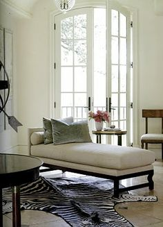 zebra rug, oversized French doors, iron ancillary, white chaise lounge with velvet pillows,crystal chandelier