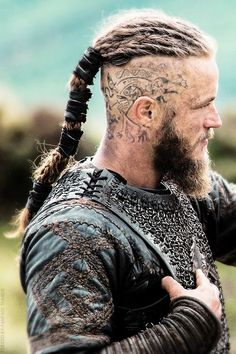 If you've watched the show Vikings you've noticed Ragnar Lothbrok's insanely rad warrior-esque hairstyle. The character portrayed by Travis Fimmel is rocking the shaved sides with long top variation of the top knot. The real question is, can this hairstyl Travis Fimmel, Vikings Ragnar, Travis Vikings, Vikings Tv Series, Vikings Tv Show, Viking Men, Viking Shop, Viking Warrior Men, Head Tattoos