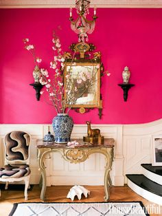 The entry of a late-19th-century house in Brooklyn is a showstopper, with walls in Benjamin Moore's Razzle Dazzle. The table and side chair — covered in vintage needlepoint — are Louis XV, and the mirror is 18th-century Italian.   - HouseBeautiful.com