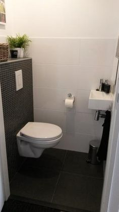 Toilet tiles up to meters, with smooth piece above. Mosaic against back wall - Modern