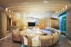 Luxurious Living Space With Contoured Ceiling And Curved Puffy Beige Sofas  And Modern Fireplace For Luxury House Designs With Twist Interior.