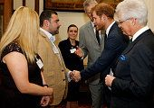 Prince Harry shakes hands with Andy Reid a former British soldier of the 3rd Batt The Yorkshire Regiment who was badly injured in Afghanistan losing...