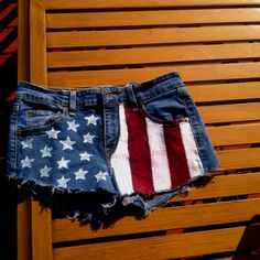 DIY Flag  1. Wash and dry jean shorts.        2. Cut a star stencil out of the piece of cardboard   3. Paint white stars along one side of the shorts with white fabric paint. 4.Tape lines to the thickness of your choice a couple inches apart on the other side of the shorts. 5. Apply white fabric paint in the untaped areas and allow to dry. 6. Apply tape on top of white and apple red fabric paint on untaped areas and allow to dry. Voila! :)