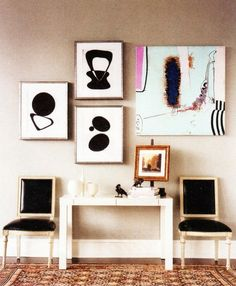 contemporary vignette--abstract gallery wall, patent leather carved louis chairs, parsons console