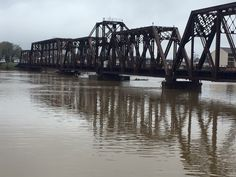 Train bridge downtown Ouachita River which  is running backwards currently and flooding still w severe storms predicted today