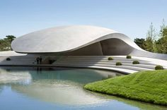 The organically-shaped Porsche Pavilion curves over a lake, shading visitors