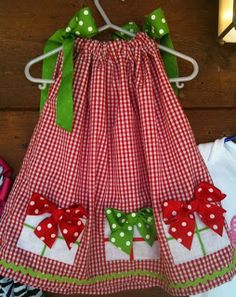 Christmas Pillow Case Dress, love! So cute too The dress has no instructions, made the designs by cutting 4 1/2 inch squares, cut 2 for each then sew 1/2 inch seam (trim and clip corners} leave opening turn out, press well, sew ribbon to finished squares, the bows are removable, making it easy to launder. Bow: http://www.sugarbeecrafts.com/2010/03/simple-bow-tutorial.html