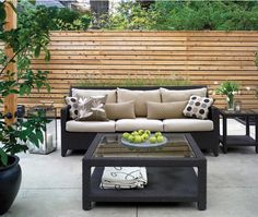 Outdoor Living Room  Sleek, faux-rattan pieces create a modern and inviting exterior lounge.  Strealined monochromatic furniture defines the seating area in this outdoor living space. Oversized glass lanterns enhance the discreet patio lights mounted on the cedar post.