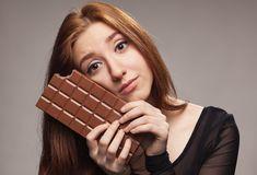 Девушка сидит в обнимку с шоколадной плиткой