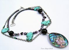 Follow your hearts desire and feel energized with this versatile necklace. Wear this original design with a white tee shirt and your favorite cowboy boots or even with evening wear! The spectacular Abalone (Paua sea shell) from New Zealand is paired with iridescent pearls and beads making this a 21 statement piece. The large turquoise colored beads slices are turquoise howlite and is believed to help cure insomnia. Genuine turquoise cube beads adorn the grey oxidized chain. I secured this…