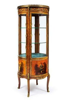 Rare model of a round freestanding salon vitrine, French Neo-Classical revival, late 19th/early 20th century. Made in rosewood, with bronze doré mounts, and a painted depiction of gallant ladies and gentlemen, one door and glass shelves. Height 154 cm, diameter 60 cm. Wien, Dorotheum, no. 584.