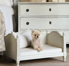 "Theodore Dog Bed. The perfect bed for your small furry friend! Darling petite scale with hand-carved pinecone finials and fluted column accents. Removable linen cushion. Dimensions: 15""H x 26""W x 20""D"