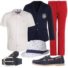 Si+salpa+subito+con+il+blazer+blu+navy+con+stemma+ricamato+sul+taschino,+la+camicia+a+mezza+manica+con+fantasia+a+piccoli+pois+blu,+e+il+pantalone+dritto+rosso+acceso.+Cappello+a+tema+con+fascia+blu+e+piccola+fantasia+di+ancore+e+timoni,+mocassini+stringati+con+cuciture+a+contrasto,+e+cintura+intrecciata.
