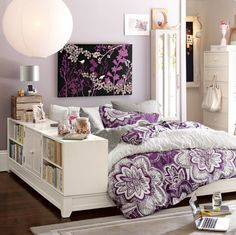 Lovely purple and white bedroom with touches of silver and black. Love the bookshelf on the side. Would like the bed higher up for additional storage.